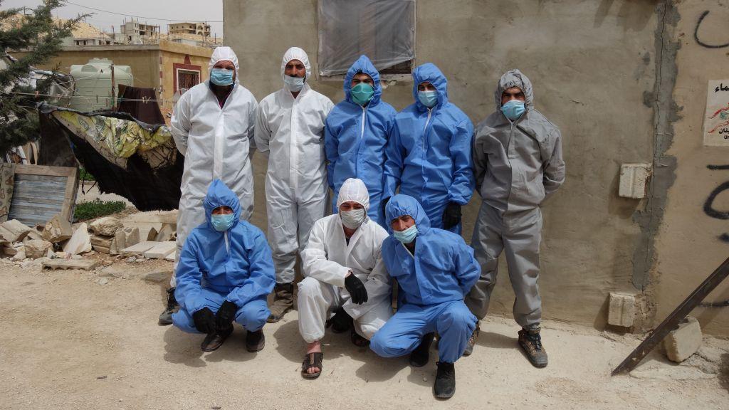Das Grünhelme-Team in Schutzanzügen und mit Masken.