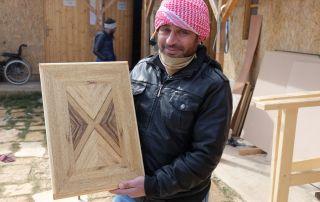 Ein Mann in einer schwarzen Lederjacke hält ein fertiges Werkstück.,
