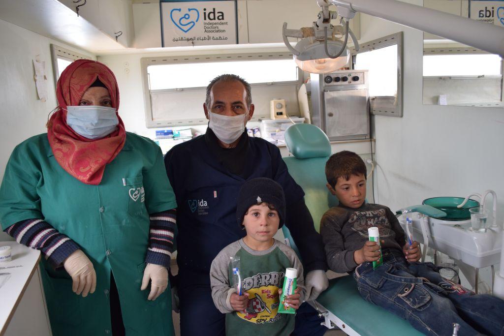 Zahnarzt Basil Orfali mit einer Zahnarzthelferin und zwei kleinen Patienten