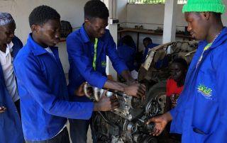 Herr Sane überwacht den Zusammenbau eines Versuchsmotors durch die Azubis von St. Eloi