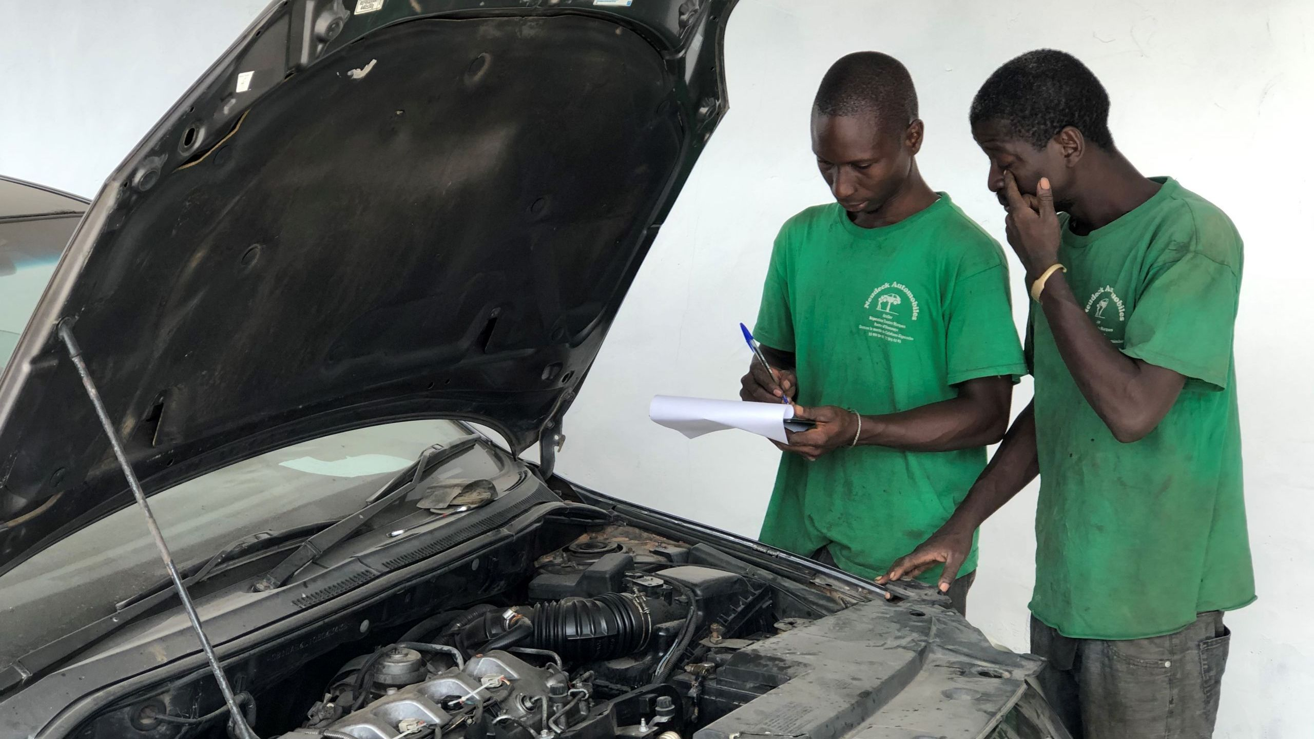 Mechatroniker L. Mendy erklärt Auszubildendem A.Sambou Fahrzeugelektronik