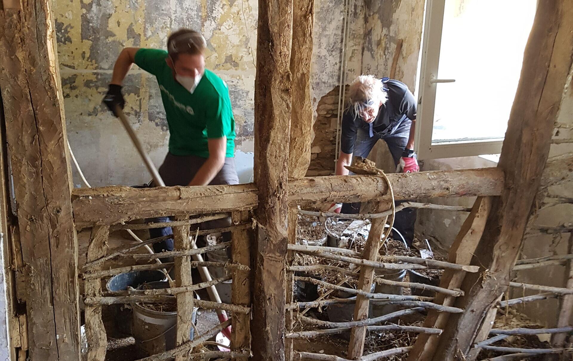 Grünhelm Max und ein weiterer Freiwilliger bei der Arbeit in dem Fachwerkhaus